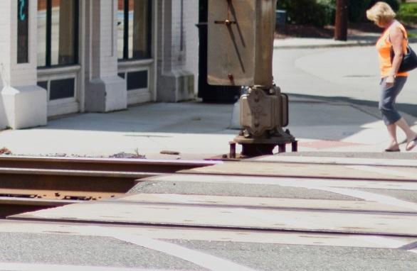 A woman walking near a precast concrete railroad crossing
