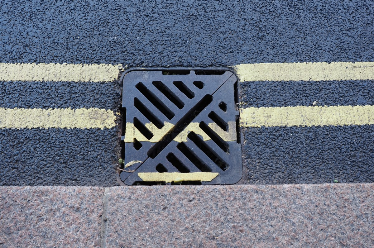 Storm drain on the side of an asphalt street with painted yellow line