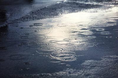 rain puddles on a pavement in city to illustrate precast concrete oil water separators